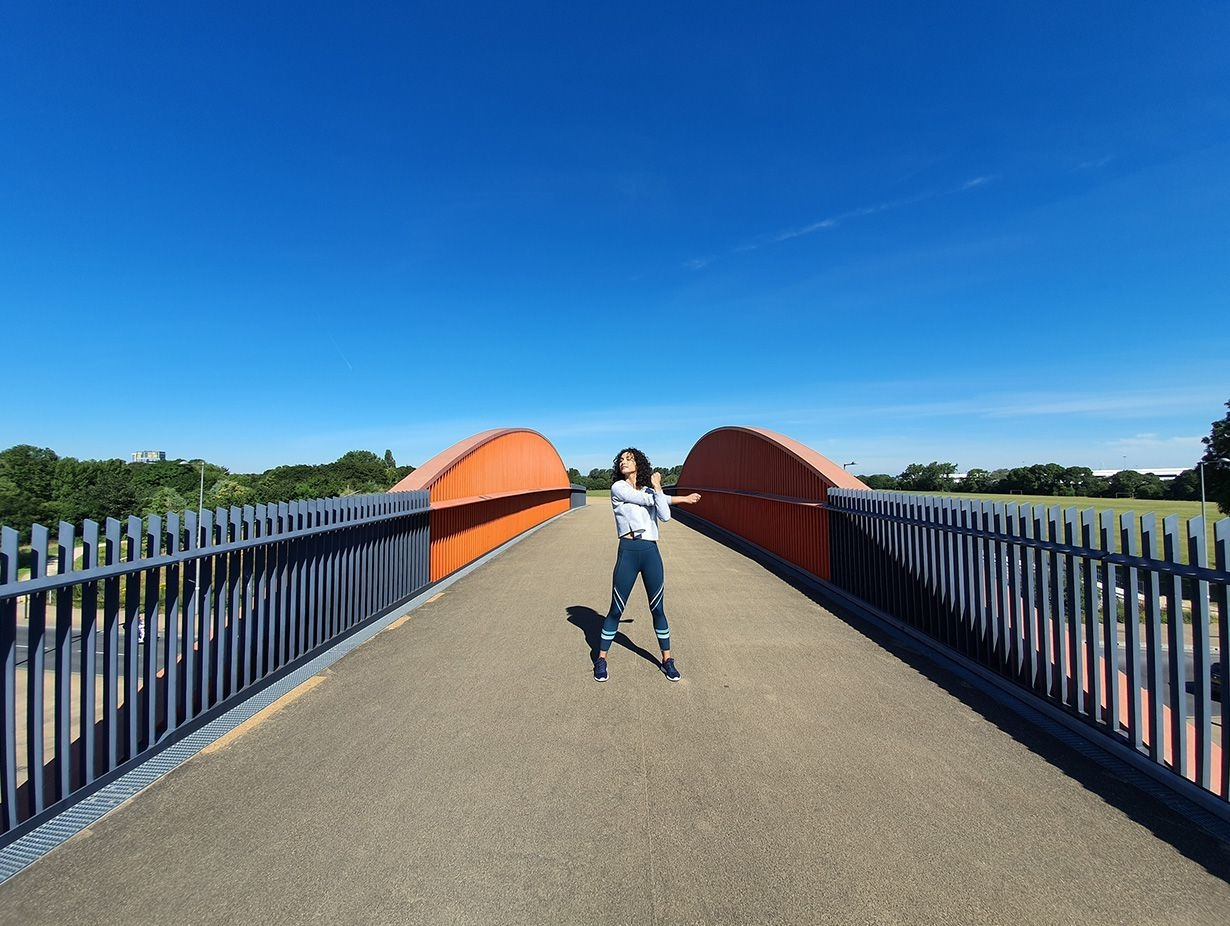Photo captured by the Ultra-wide Camera of a woman stretching on a bridge with grey gating and orange accents against a bright blue sky