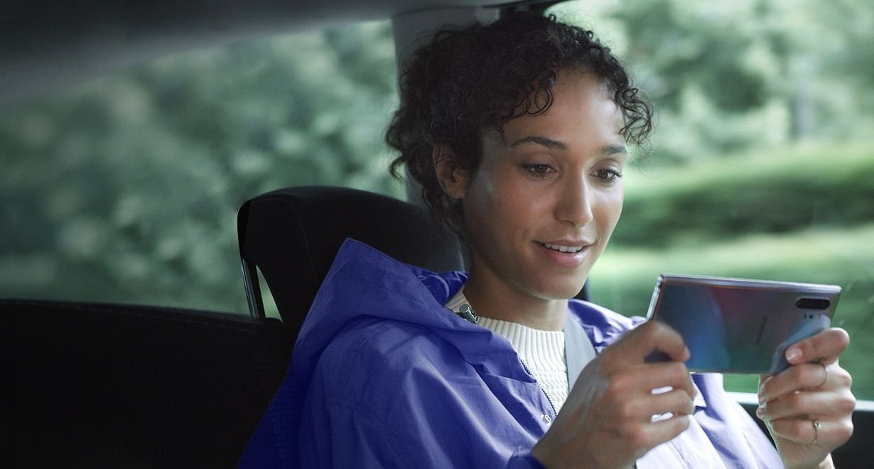 Woman sitting in a car holding Galaxy Note10 plus in landscape mode. Download manager notifications appear showing three large files being downloaded at the same time thanks to the fast data capabilities
